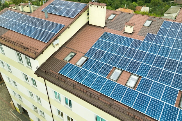 アパートの建物の屋根に取り付けられた青い太陽電池パネルを備えた太陽光発電所の空撮。