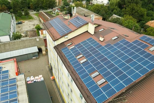 아파트 건물 지붕에 파란색 태양광 패널이 장착된 태양광 발전소의 공중 전망.