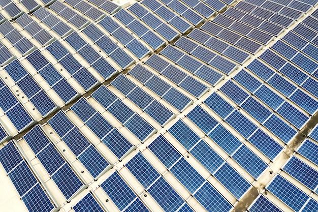 Аэрофотоснимок солнечной электростанции с голубыми фотоэлектрическими панелями, установленными на крыше промышленного здания.