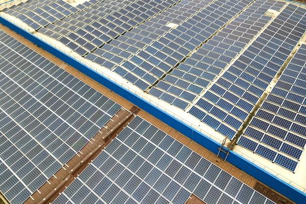 Аэрофотоснимок солнечной электростанции с синими фотоэлектрическими панелями, установленными на крыше промышленного здания.