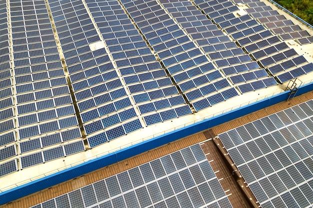 Вид с воздуха на солнечную электростанцию с синими фотоэлектрическими панелями, установленными на крыше промышленного здания.