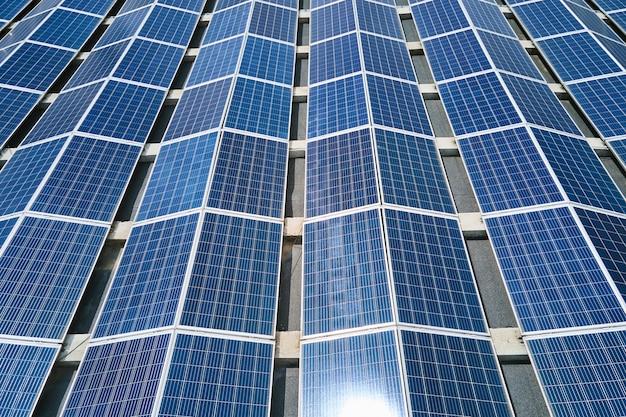 녹색 생태 전기를 생산하기 위해 산업 건물 지붕에 파란색 태양광 패널이 장착된 태양광 발전소의 공중 전망. 지속 가능한 에너지 개념의 생산.