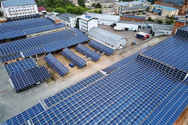 緑の生態学的電力を生成するために工業用建物の屋根に取り付けられた青い太陽光発電パネルを備えた太陽光発電所の航空写真。持続可能なエネルギーの概念の生産。