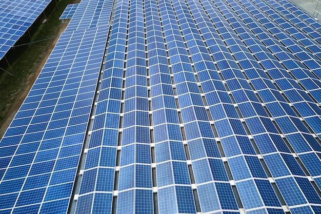Вид с воздуха на солнечную электростанцию с синими фотоэлектрическими панелями, установленными на крыше промышленного здания для производства экологически чистой электроэнергии. производство концепции устойчивой энергетики.