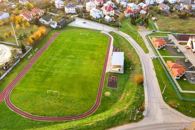 赤いランニングトラックと緑の芝生のサッカー場のあるスポーツスタジアムの空撮。