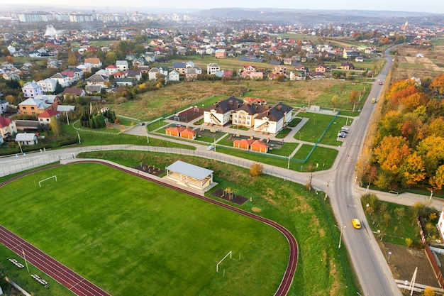 Вид с воздуха на спортивный стадион с красными беговыми дорожками и футбольным полем с зеленой травой.