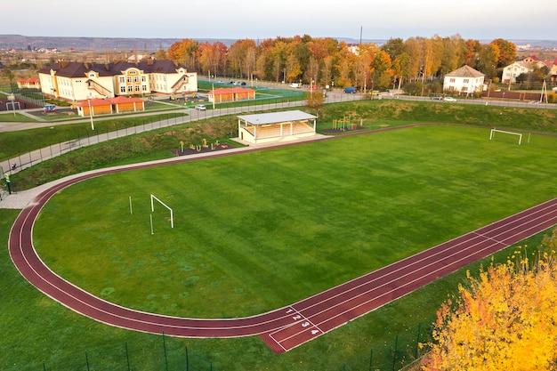 빨간색 달리기 트랙과 푸른 잔디 축구장이 있는 스포츠 경기장의 공중 전망.