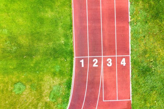숫자가 있는 빨간색 달리기 트랙과 잔디 축구장이 있는 스포츠 경기장의 공중 전망.