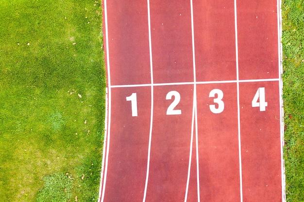 Вид с воздуха на спортивный стадион с красными беговыми дорожками с числами на нем и футбольное поле с зеленой травой.