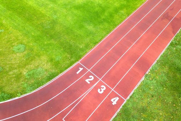 숫자가 있는 빨간색 달리기 트랙과 푸른 잔디 축구장이 있는 스포츠 경기장의 공중 전망.