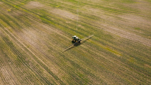 Аэрофотоснимок распыления машины, работающие на зеленом поле.
