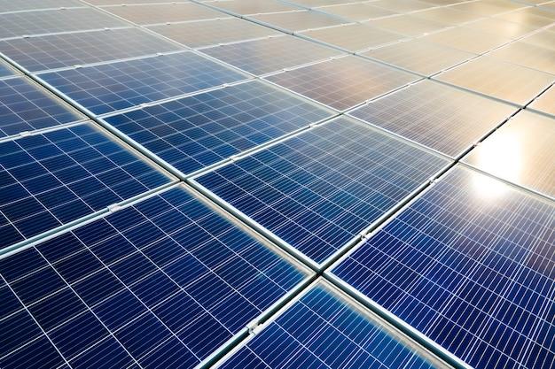 Вид с воздуха на поверхность синих фотоэлектрических солнечных панелей, установленных на крыше здания для производства экологически чистой электроэнергии. производство концепции возобновляемой энергии.