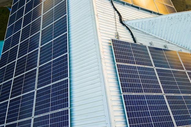 깨끗한 생태 전기를 생산하기 위해 건물 지붕에 장착된 파란색 광전지 태양 전지판 표면의 공중 전망. 재생 에너지 개념의 생산입니다.