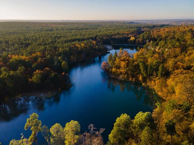 Вид с воздуха на осенний лес у реки днем