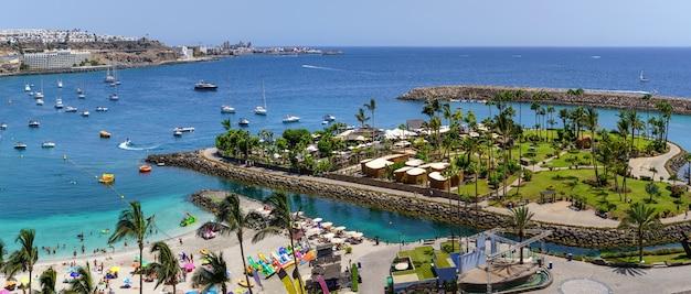 Вид с воздуха на пляж летом с лодками и зонами отдыха. гран-канария, испания. испанец.