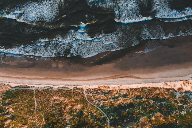 砂浜に打ち寄せる海の波と美しい海岸線の空撮