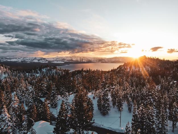米国カリフォルニア州の雪に覆われた夕日に撮影された美しいタホ湖の空撮