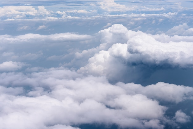 Вид с воздуха на большие белые облака и дождь облака на голубом небе над голубым океаном