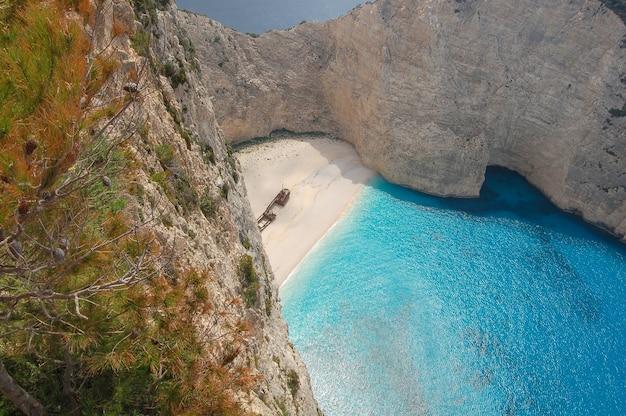 海岸の古いボートの残党と崖に囲まれた青い海の空撮