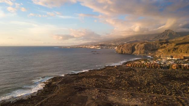 Вид с воздуха на побережье и пена морских волн, сухая местность и тропы, канарские острова