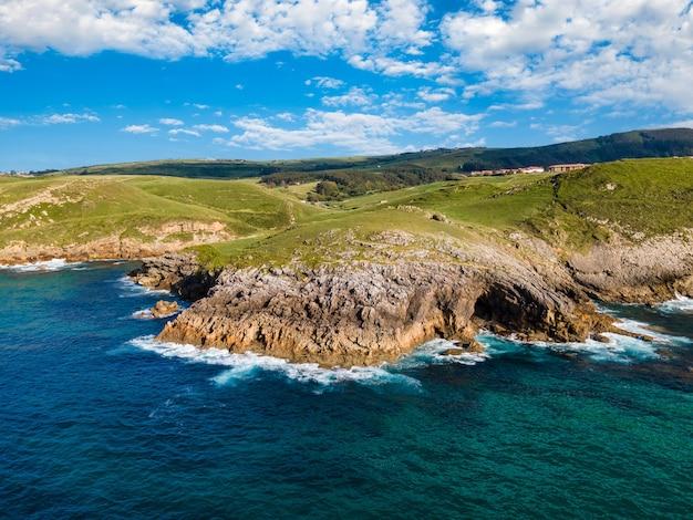 바다와 바위 동굴에 절벽이 있는 해안의 공중 전망. 칸타브리아.