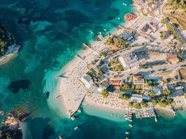 Вид с воздуха на побережье курортного города ксамил в солнечный летний день. албания.