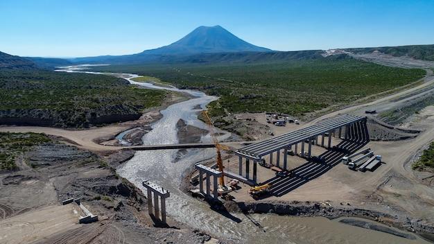 ラテンアメリカの川に架かる新しい橋の建設の航空写真。
