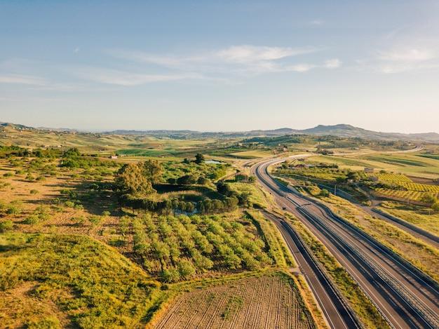 車が通り過ぎるイタリアの高速道路の航空写真