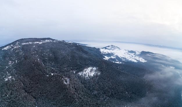 Вид с воздуха на мистический пейзаж зимнего горного леса в пасмурный морозный день. представление о суровой красоте северных стран. copyspace