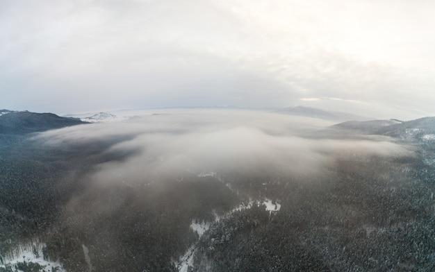 曇った凍るような日に冬の山の森の神秘的な風景の空撮