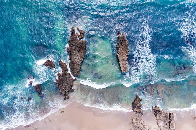 Аэрофотоснимок берега океана с волнами, разбивающихся о скалы и пляж с белым песком