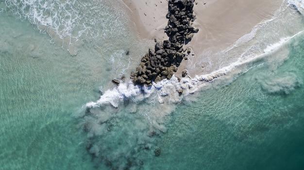 해변에서 바위 더미에 의해 침입하는 파도의 공중보기