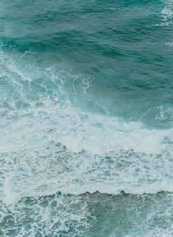 Вид с воздуха на океан с волнами и скалами в яркий день, расслабляющая сцена в голубых тонах