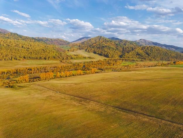 収穫された冬の作物のフィールドと絵のように美しい秋の山々の空撮。明るい秋の色、