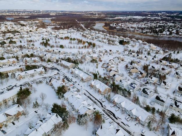 雪の降る冬の日の小さな町の住宅街の空撮
