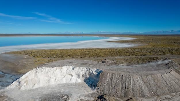 Вид с воздуха на соляную гору с солевым раствором на заднем плане.