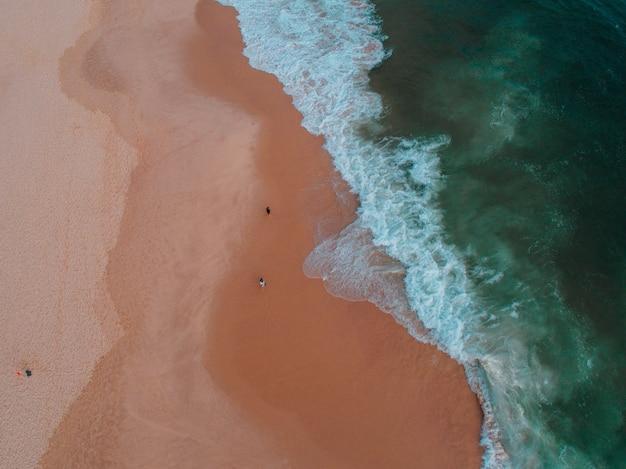 Вид с воздуха на берег моря с несколькими людьми на нем