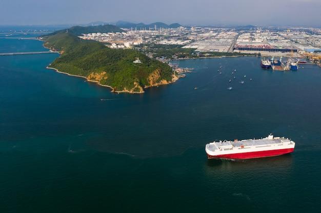 新しい車をロードする船の空撮。自動車コンテナ船の海外サービス。海上輸送によるプレハブ自動車の輸送事業。