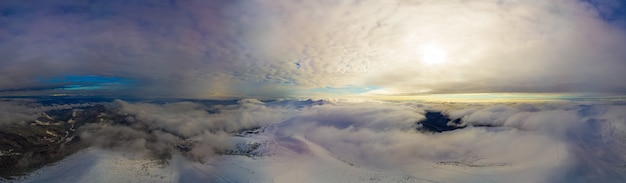 緑豊かな白い雲に囲まれた雪の斜面と丘の見事な冬のパノラマの空撮。厳しい冬の自然を魅了するコンセプト