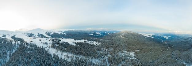 緑豊かな白い雲に囲まれた雪の斜面と丘の見事な冬のパノラマの空撮
