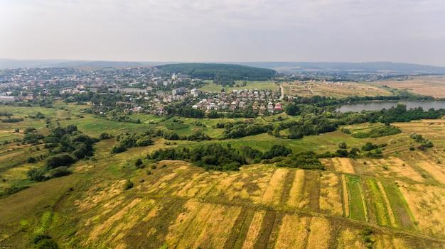 Вид с воздуха на летнюю сельскую местность. полет над зеленым полем и городом.