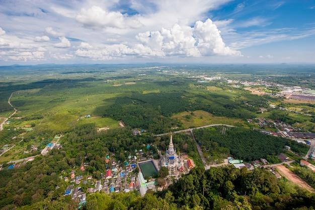 タイガーケーブ寺院の空撮。緑の野原と青空を背景に雲。