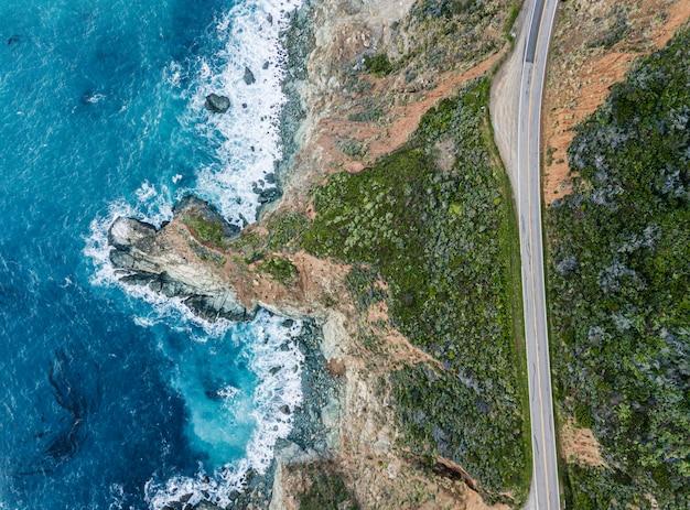 道路の横の岩に砕ける波の空撮。波が岸で砕ける間、明るい青色と暗い青色の水が泡立ちます。深海。