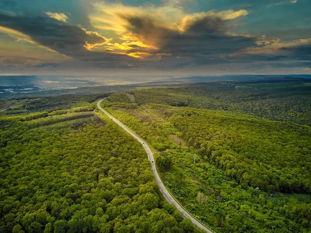 Вид с воздуха на густой лес осенью с прорезанием дороги