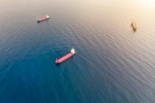 Вид с воздуха на три контейнеровоза в море, занимающихся перевозкой грузов по воде. доставка груза в порт. водный транспорт. морская доставка контейнеров. водные суда стреляли сверху