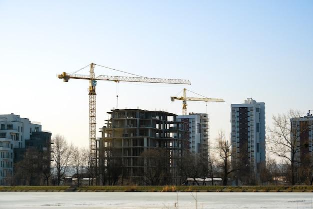 建設中のタワークレーンと高層住宅の空撮。不動産開発。