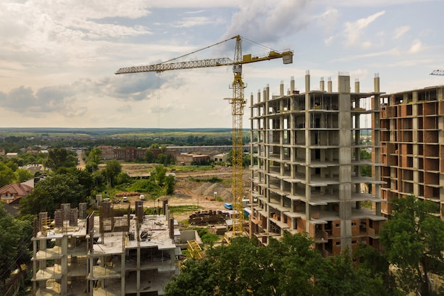 タワーリフトクレーンと都市で建設中の高層マンションのコンクリートフレームの空撮。都市開発と不動産成長のコンセプト。