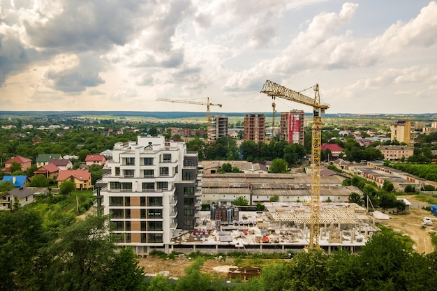 Аэрофотоснимок башенного подъемного крана и бетонный каркас строящегося многоквартирного жилого дома в городе. концепция городского развития и роста недвижимости.