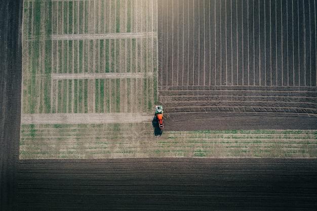 耕作された農地で作物の直接播種を行うトラクター搭載播種機の航空写真。