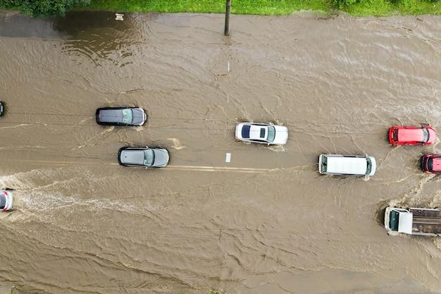 빗물로 침수된 도로를 운전하는 교통 차량의 공중 전망.